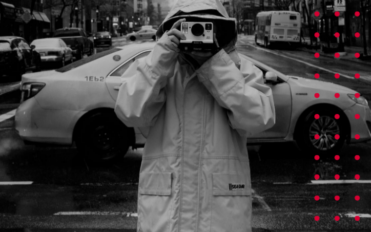 Man holding camera to face viewer in black and white